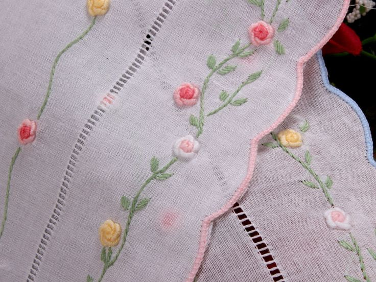 Bullion roses embroidery with stem stitch vines and satin stitch leaves.
