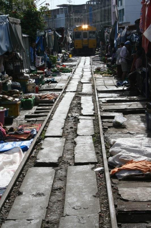 In Thailandia accade anche questo: il mercato tra i binari della ferrovia, al passaggio del treno tutto si ferma per riprendere subito dopo il suo passaggio