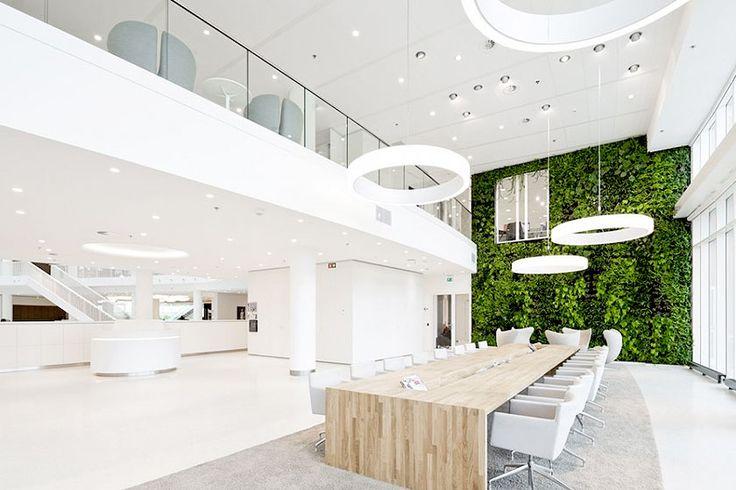 Een groene 'Living Wall' in dit superstrakke, zeer witte kantoorinterieur. De planten zorgen voor de juiste accentkleur. Gecombineerd met een mooie houten tafel maakt het een goed voorbeeld van een natuurlijker kantoor. - More office interior inspiration on http://www.stylingblog.nl
