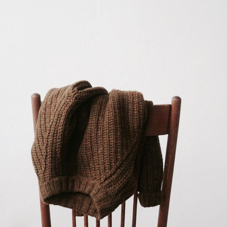 a photo of a brown sweater hanging over the back of a chair