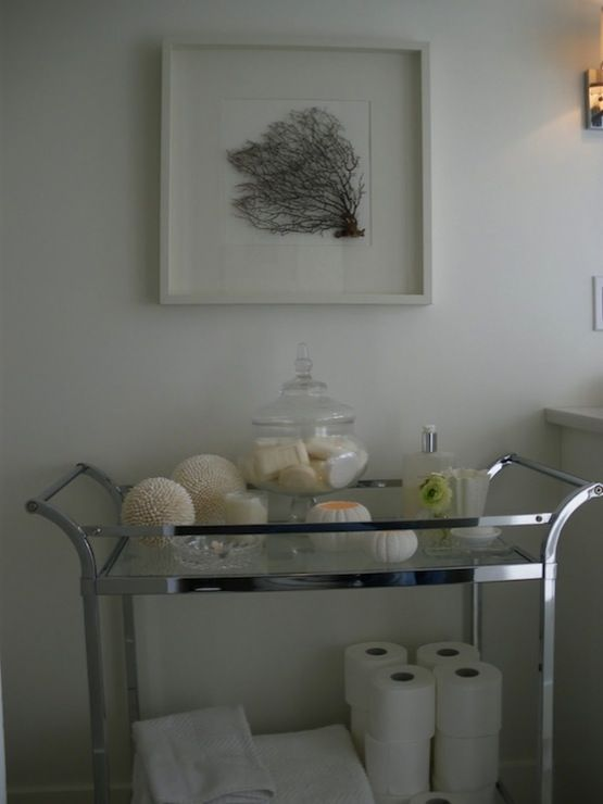 Suzie: Moth Design -Pottery Barn bar cart used to house bathroom accessories! Seafan framed in white shadow box, glass canisters, towels, candles and soaps.