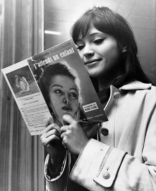 Anna Kerina in Une Femme Est Une Femme (1961) with feline flicks and beige trench