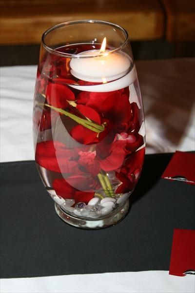 Centerpieces displayed a water submerged orchid, topped with a floating candle. Shades of white rocks held the orchid in place. On either side of the vase (not shown) were two square votive candle holders with matching white rocks and a red candle. Centerpieces sat on a white table cloth and black table runner.