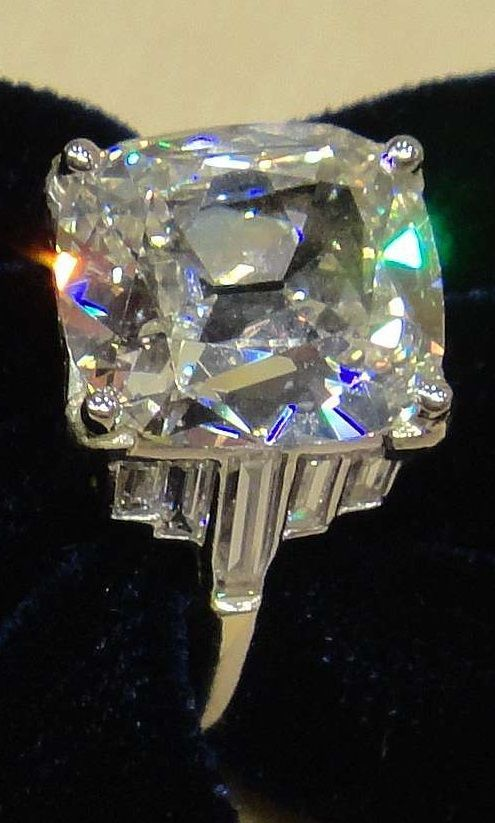 An Art Deco platinum and diamond ring, circa 1930. Set to the centre with one antique cushion cut diamond weighing 5.05 carats and further set with baguette cut diamonds. #ArtDeco #ring