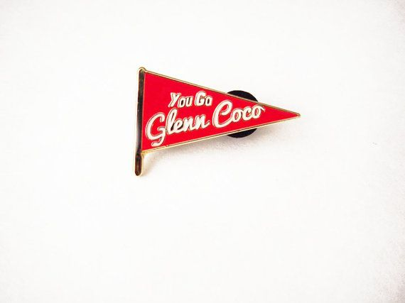 Glenn Coco? FOUR for you, Glenn Coco! You go, Glenn Coco! - Damian  This cute enamel pin is shaped like a small hand held pennant flag , the pin is emblazoned on the front with one of my favorite lines from the movie Mean Girls: You Go Glenn Coco!. Pin is cherry red with text done in white outlined in gold. Pin has a double pin back for added stability and closes shut with two small rubber clutches. Piece is nice and shiny and glistens when it catches the light!  Pin measures approximately…