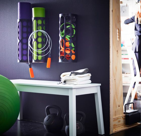 A VARIERA plastic bag container can be spray painted black, attached to a black wall and filled with colorful gym gear including a yoga mat, foam roller and stretch bands.