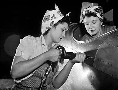 "Two women work together building planes in a factory to support the war effort while the men are abroad. ""Rosie the Riveter"" Photo by Harold M. Lambert. - WWII propaganda photo, USA, women war workers"