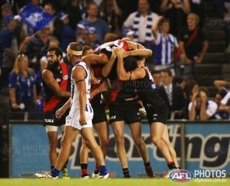 David Myers celebrates with team mates while the dejected Ben Cunnington walks off during the AFL Round 01 match between the North Melbourne Kangaroos and the Essendon Bombers at Etihad Stadium,
