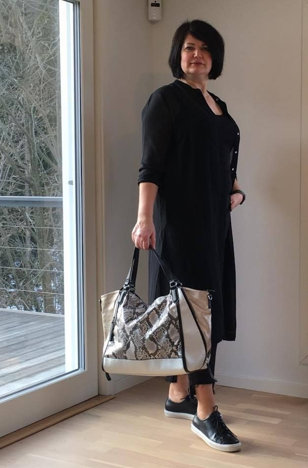 Black outfit with a python-printed bag