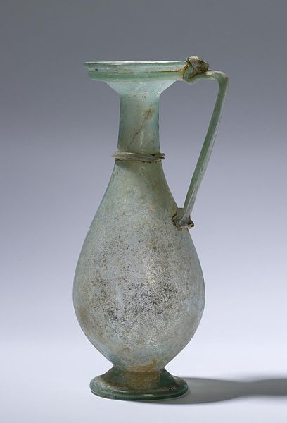 Roman jug - used to hold wine or water at the dinner table. Made of free-blown glass, this example is composed of a green-toned, slightly iridescent glass and is decorated with a thread around the neck and another around the mouth, made by trailing molten glass around the vessel when it was still hot. Date4th century (Late Antique)