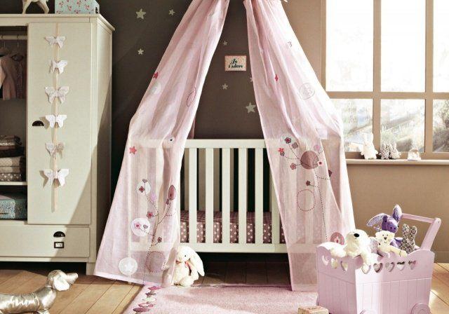 murs gris et rideaux roses dans la chambre bébé