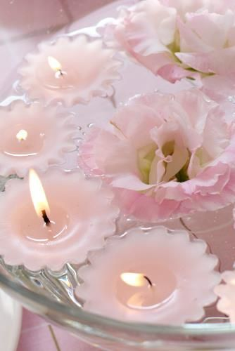 Pink floating candles & simple blooms form a romantic centerpiece.
