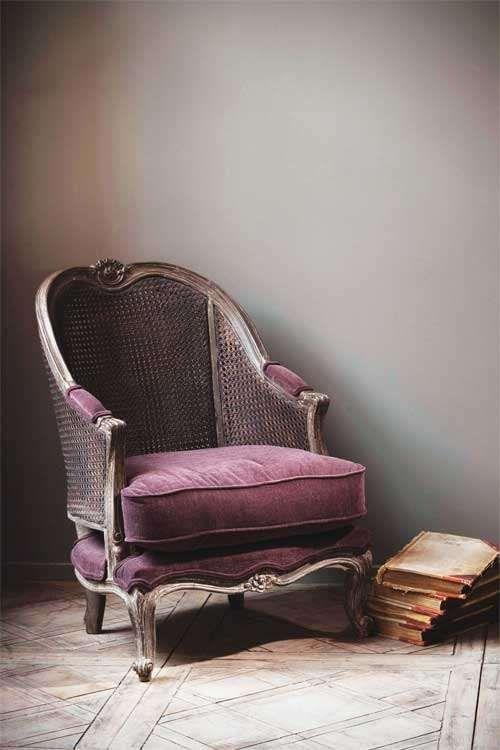 Vintage armchair covered in dark mauve velvet.