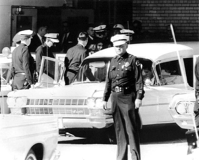 """""""Thirty-four years old and one hour a widow,"""" former First Lady Jacqueline Kennedy leaves the Emergency Room of Parkland Hospital in Dallas, Texas with her husband's body to begin the trip back to Washignton, D.C."""