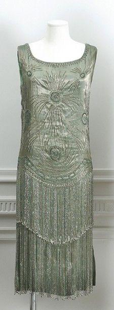 Anonyme circa 1925 Robe en soie métalisée vert d'eau rebrodé de perle de verre argent, turquoise à motif Art- Nouveau finissant par deux rangées de franges séparées par de petites perles (quelques manques)… - Cornette de Saint Cyr maison de ventes - 05/07/2016