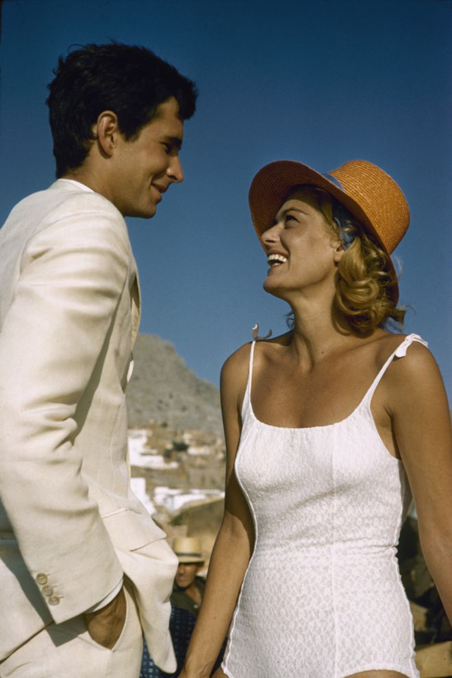 "In the photo Melina Mercouri is pictured with her co-star Anthony Perkins on the set of 1962's ""Phaedra,"" which was also directed by her future husband Jules Dassin. Mercouri exemplifies '60s style in her white, fitted swimsuit, but we're really loving her cute straw hat and that huge grin -- and that cloudless sky is the perfect backdrop."