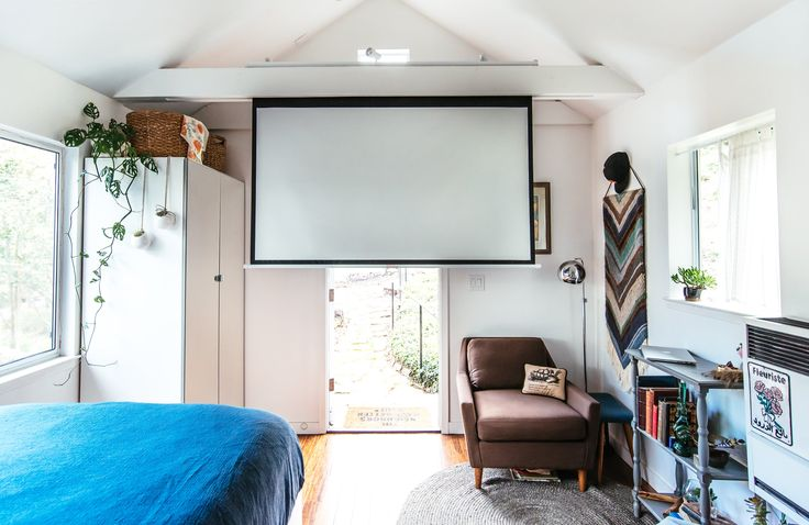 For foggy Bay Area nights there is a huge pull-down screen hidden in the beam to watch projected movies. The PAX Mirror Closet from IKEA adds storage in the corner.