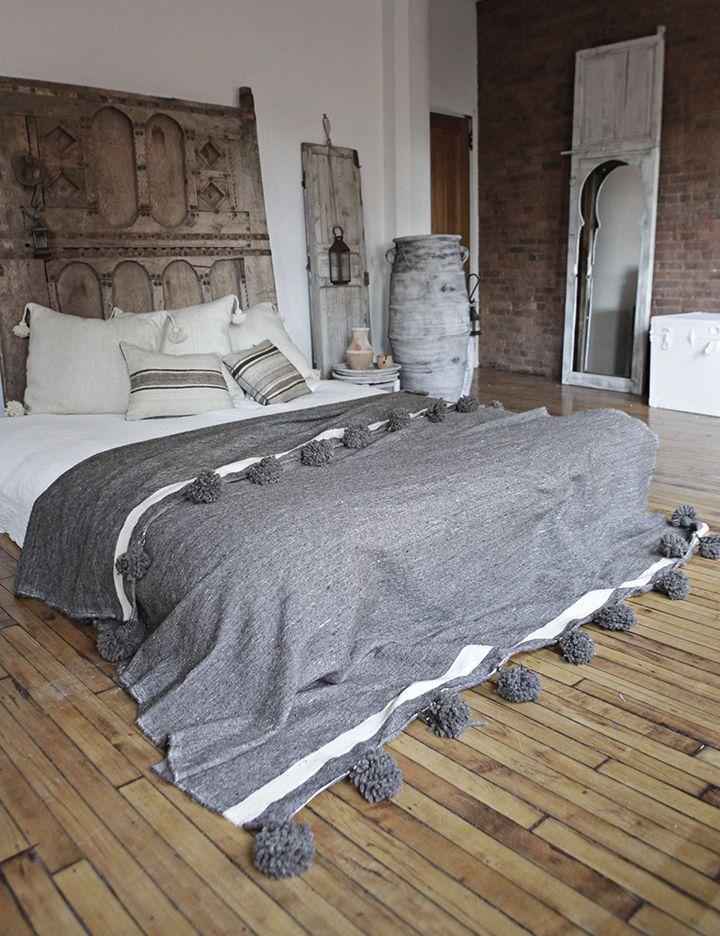 Moroccan style bedroom. Wool Pom pom blanket, Berber mirrored door, large wooden headboard