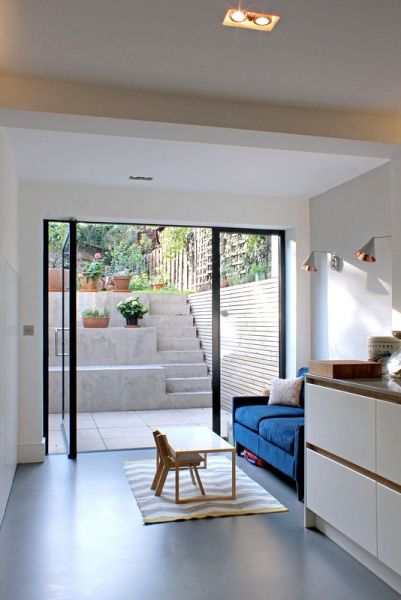 Milton - View from kitchen looking out through glass pivot door onto new external space with concrete steps to garden.