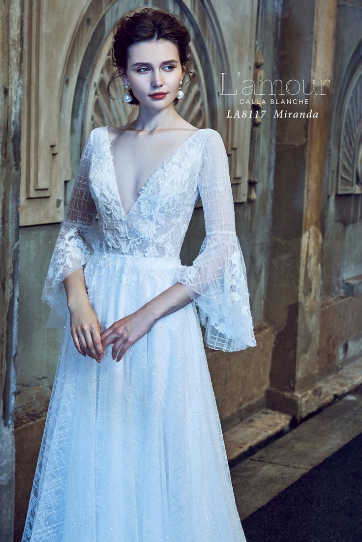 LA8117 Miranda Sparkle encrusted fabric makes up this stunning wedding dress.  Fashioned with bell sleeves, v neck and sheer bodice this pretty ivory gown suits almost any wedding theme.  Straight sleeves can be ordered upon request.  #lamourbycallablanche #callablanche #shimmertulle #bellsleeve #bride #bridalgown #ballgown #vneck #naturalwaist #ido #herecomesthebride #3/4sleeve