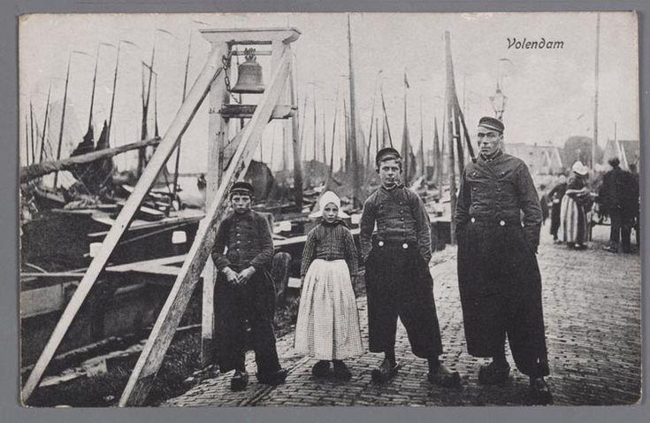 Twee mannen met pijp en een jongen en een meisje, allevier in dracht, poseren bij de klokkenpaal aan de Haven. De klokkenpaal werd geluid bij mist en bij een trouwerij. 1900-1908 #NoordHolland #Volendam