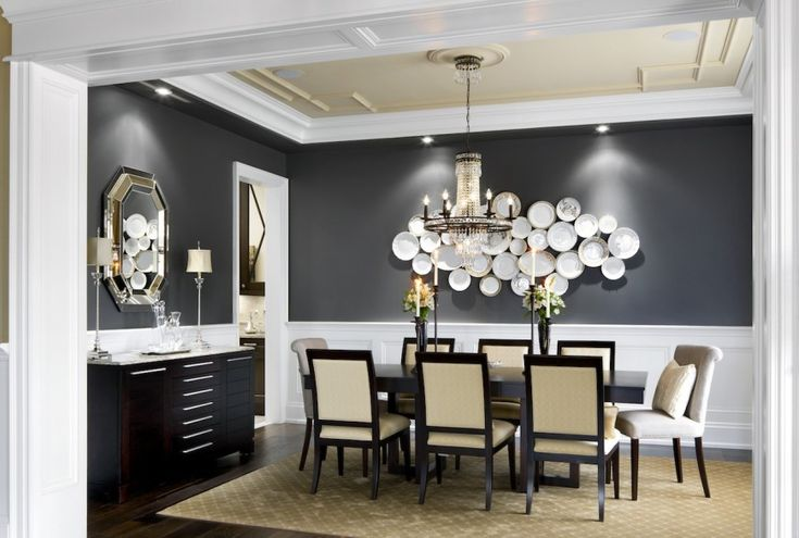 The wall behind this contemporary dining set in black and beige is decorated with plates of varying sizes and patterns to create a plate wall. The lower half of the wall has elegant white wainscoting.