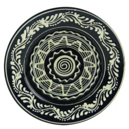 """Carefully handmade from glazed Baia Mare ceramic, this plate came to life from the hands of the potter craftsmen, so passionate for their trade.The ultramarine blue background color is complimented by hand painted white floral motifs and the text customization """"Romania. To certify its authenticity, the plate is signed on the back by Cornel Sitar, the popular craftsmen."""