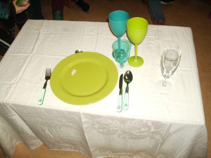 kleuters dekken na uitleg van de ober zelf een tafel, met de duim meten ze of alles ver genoeg van de tafelrand ligt.