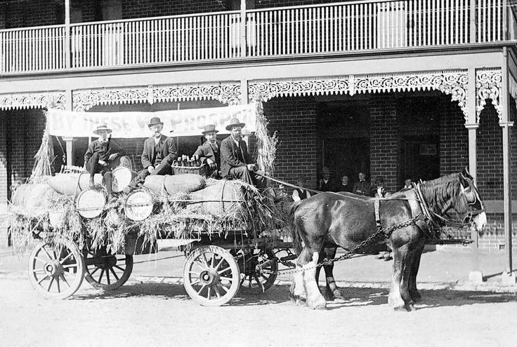 A decorated brewery wagon (banner: By these we prosper) outside the Bull and Mouth Hotel, Horsham in 1915.
