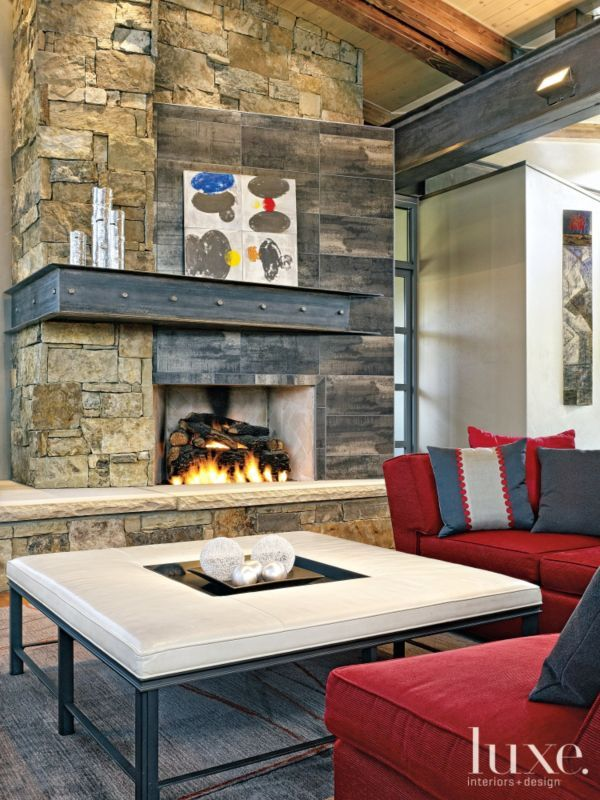 a tom stephens painting pops against the steel stone and tile fireplace