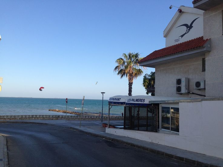 Vista de playa y bahia, desde la esquina del edificio de Apartamentos Ornis, al inicio de la zona peatonal del Paseo Maritimo, Sus aguas son un lugar ideal para la practica de todo tipo de deportes nauticos y pesca.