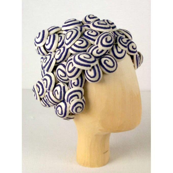 'Krullenhoed'. Irene van Vugt. De hoed bestaat uit vilten bolstaande ronde lapjes (diameter ±5.0 cm), waarop met paars telkens een spiraal gestikt is. Al deze bolvormpjes zijn tot een bolvorm aan elkaar genaaid en zien eruit als papilotten. De hoed is met paarse zijde gevoerd, die een bodem heeft waarop een oudrose ribslint geplakt is met de naam 'Irene van Vugt'. In de kleuren: ecru en paars.Collectie Textielmuseum Tilburg.