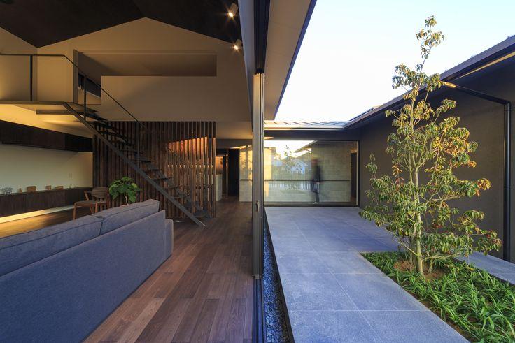 富の原の家のリビング・・・ 中庭を挟み南の棟が有り、中庭はコの字型に囲まれた外部空間です。 南の棟は平屋の為、北の棟のリビングにも南からの光が差し込みます。 リビングの天井は5mと高めです。空間が垂直方向と中庭の水平方向へと広がります。 、#リビング、#中庭、#ソヨゴ、#タイル、#階段、#スケルトン階段、#鉄骨階段、#木製格子、#シークエンス、#和モダン、#シンプル、#建築家、#設計事務所、#住宅、#注文住宅、#デザイン、#ミニマル、#家、#residence、#simple、#minimal、#japanese、#architec、t#design#