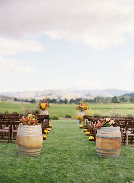 This decor is perfect for a country wedding. The barrels are tasteful, and the pops of yellow are perfect.