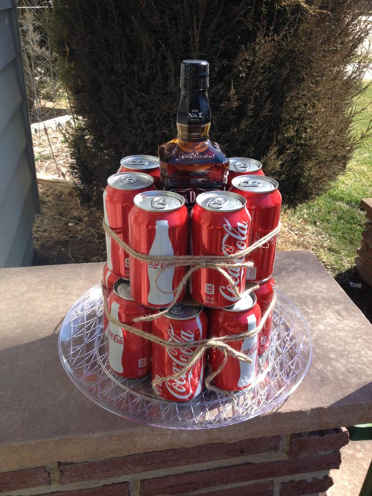 Jack & Coke Cake! The bottom layer is 9 cans of Coke tied together with jute. Placed on a sturdy try for transport. There is a sturdy circle piece of cardboard on top between the two layers. The second layer is 7 cans of Coke also tied together with jute. In the middle of the top layer is a 750ml bottle of Jack Daniels. This will be wrapped in a clear plastic gift bag and tied with jute.