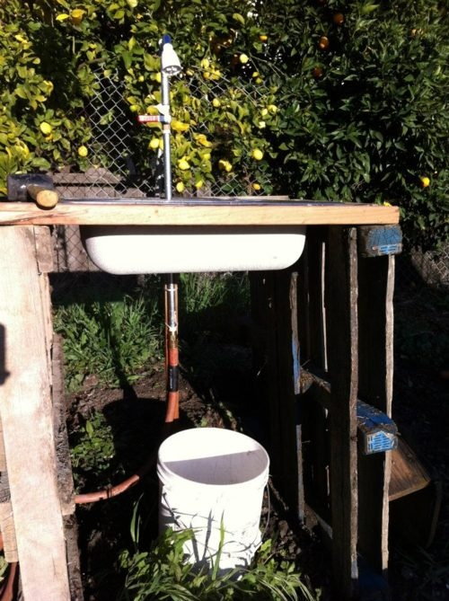Simply made. Pallets, old sink, hose, and bucket for catching the water to reuse on the garden. Simple. Effective. Thumbs up!