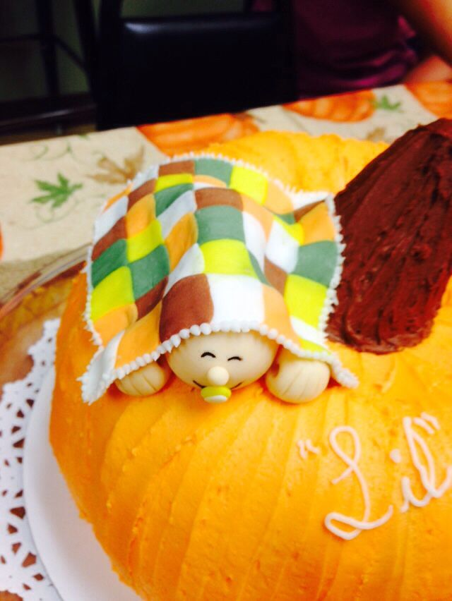 Close-up of baby on the pumpkin cake w/ fall quilt!