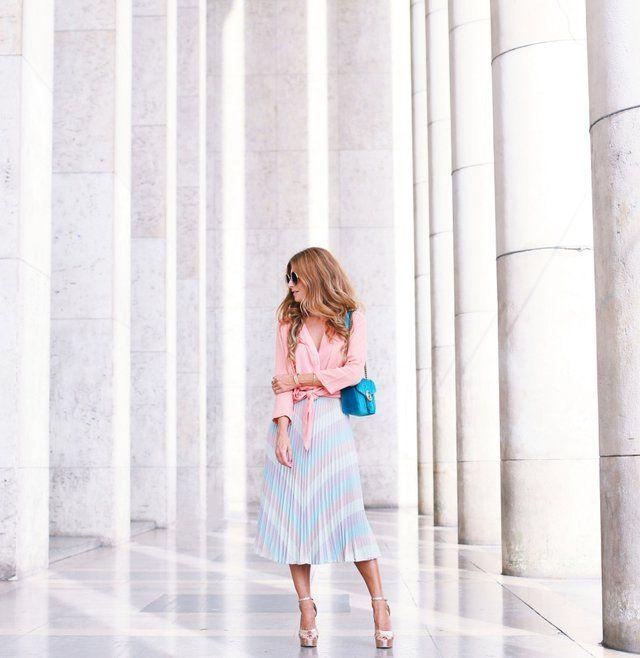 Este look combina una blusa anudada de color rosa,con una  falda midi de Total Intrópiaade tablas en tonos pastel muy voluminosa y llamativa. Además lleva un bolso turquesa de Gucci, gafas de sol Chloe  y sandalias doradas contrastantes de Zalando, accesorios geniales para este outfit.