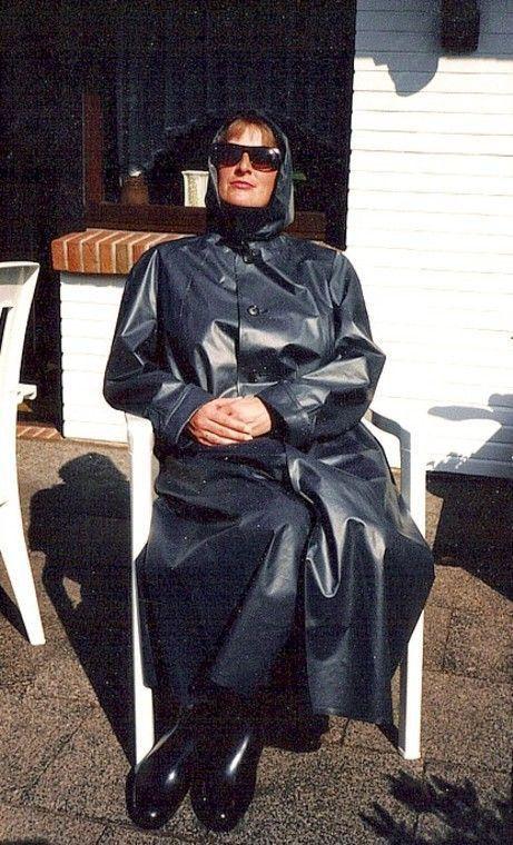 Sexy rainwear and rubberboots wearing woman !! Enjoying the sunshine in her rubber mackintosh.!!