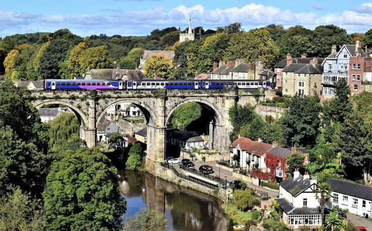 The Northern Rail train crossing the bridge into Knaresborough station.  Knaresborough  is an historic market town, spa town and civil parish in the Borough of Harrogate, North Yorkshire, England. Historically part of the West Riding of Yorkshire, it is located on the River Nidd, 4 miles (6.4 km) east from the centre of Harrogate.  An elegant stone viaduct over the River Nidd was built to carry a branch of the Leeds & Thirsk Railway. The four-span bridge stands 78ft high above the water, ...