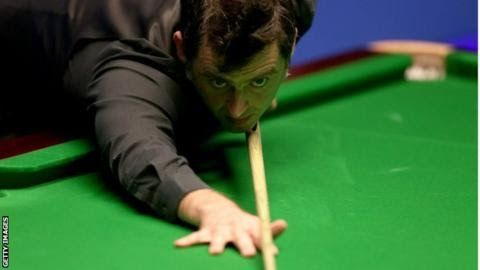 Ronnie O'Sullivan is a five-time world champion  Ronnie  O'Sullivan let a spectator who evaded security and ran around the table  take his last shot as he won in the third round at the English Open.  The  woman entered the playing arena at the Barnsley Me