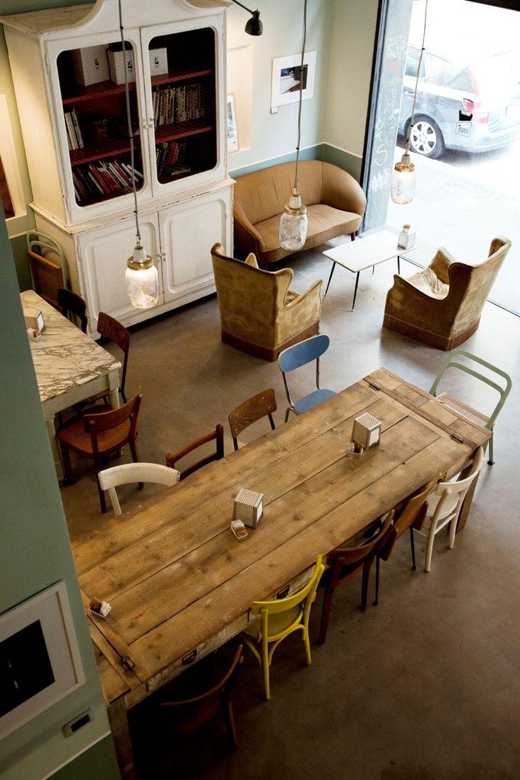 Reforma de cafetería realizada con muebles y objetos reciclados. Lámparas-tarro, mesa de tablones de madera, etc.