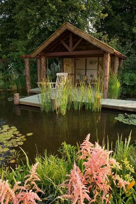 HAMPTON COURT FLOWER SHOW 2006: DESIGNER - PETER SIMS. A JETTY ACROSS A POND, POOL AND WOODEN SUMMERHOUSE, BOATHOUSE