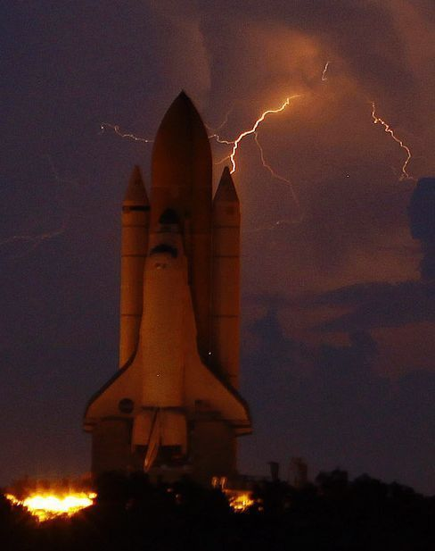 Space Shuttle Discovery starts its rollout from the Vehicle Assembly Building, Kennedy Space Centre, Cape Canaveral, Florida, during a thunderstorm.