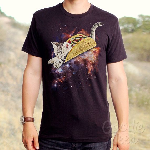 Its a taco, its a cat...its a TacoCat in space!! What WILL they think of next? This spaceadelic tee shows a cute kitty in a giant taco floating in