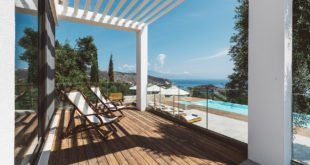 GREEK STYLE VILLAS - Deck chairs on wooden decking with cypress trees in the distance.