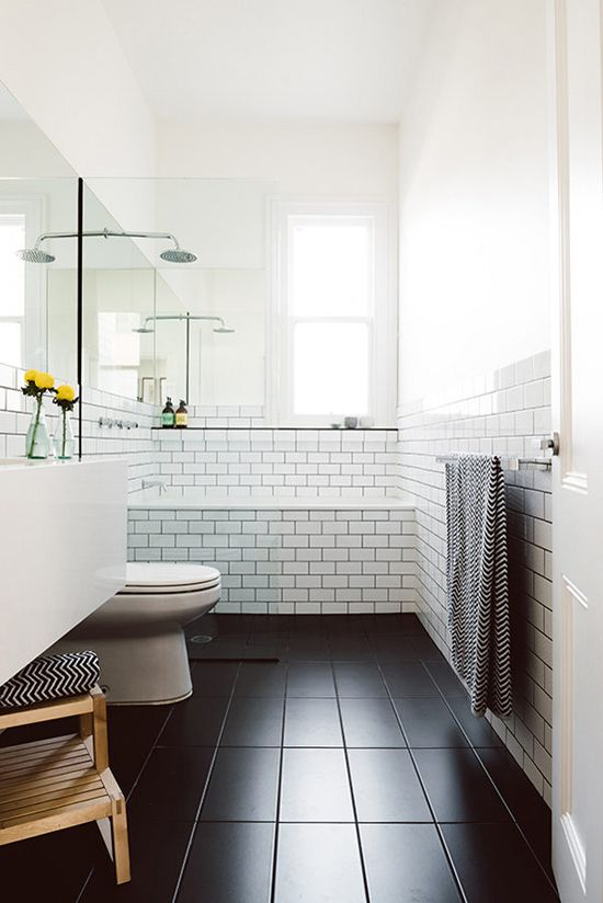 Here's another smart idea. An open shower placed right before the bathtub and separated by the aligned toilet and vanity with a clear glass. That way the bathroom stays open and airy but still holds the double quality of both bathing and showering at the same spot. The black floor and the sleek surfaces add depth to the room. | Techne