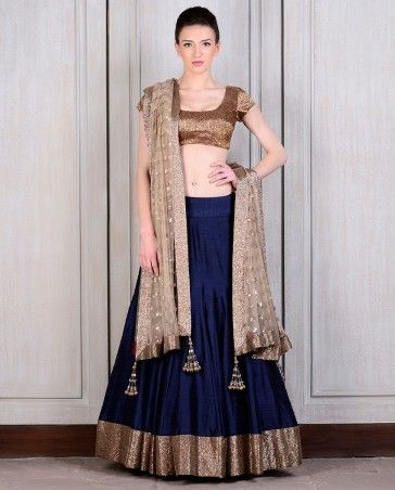 Navy blue raw silk lehenga teamed with an antique-finish golden blouse and a beige net dupatta with butti work all over.
