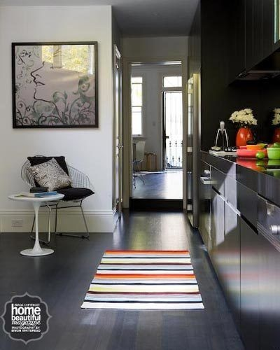 Black polyurethane cabinetry is paired with Caesarstone benchtops in jet black in this dramatic kitchen. A Missoni rug adds a splash of colour.
