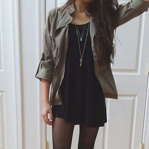 Grunge look with the green military jacket, layered necklaces, black dress, messy hair, and black tights.